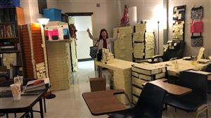 Teacher standing in the classroom covered in post-it notes